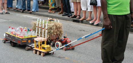 Two Model Tractors with Separate Carts Carrying Canes & Bottles Through the Streets of Holetown at Holetown Festival, St. James, Barbados Pocket Guide
