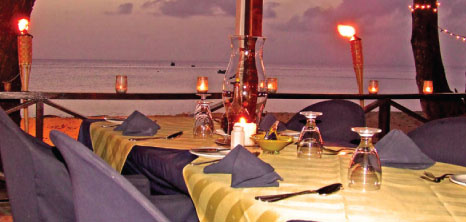 Dinner Tables Set Amidst a Backdrop of Burning Bamboo Torches, Il Tempio Restaurant, Fitts Village, St. James, Barbados Pocket Guide