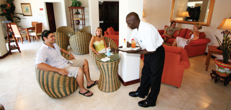 Couple Being Served Drinks in the Lobby of a Hotel, Barbados Pocket Guide